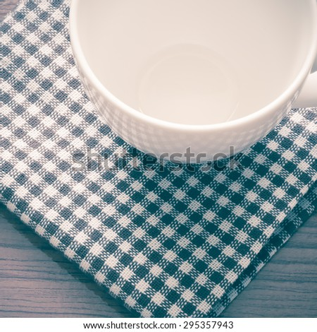 empty coffee cup on brown kitchen towel and wood table vintage style - stock photo