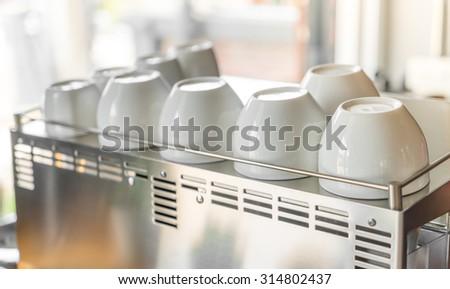 Empty coffee cup on coffee machine - stock photo