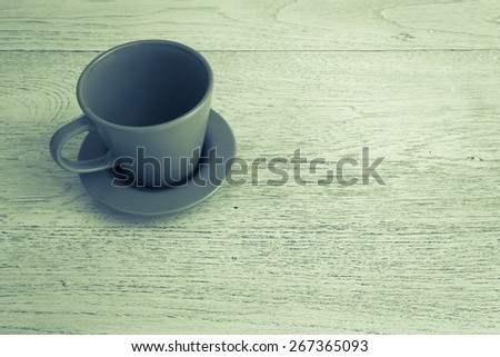 Empty coffee cup on old wooden table with vintage style - stock photo