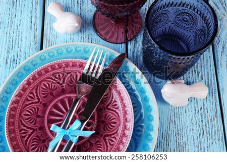 Empty colorful plate, glasses and silverware set on wooden table - stock photo