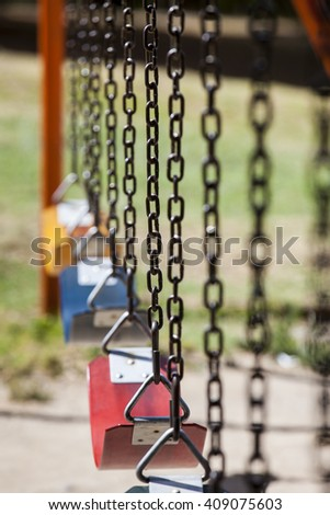 Empty colorful swings at the park - stock photo
