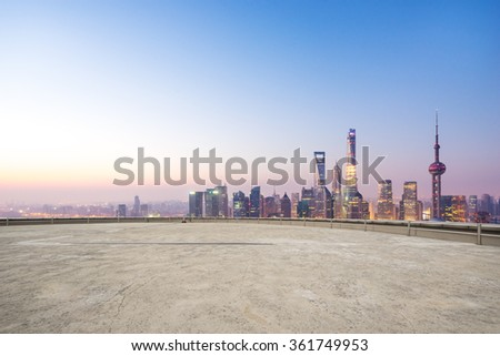 empty concrete floor and cityscape in blue sky at dawn - stock photo