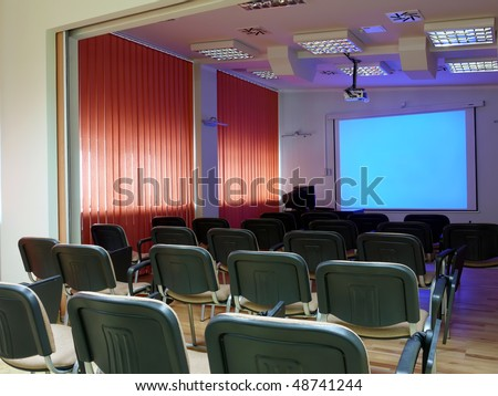 Empty conference room with blank projector screen - stock photo