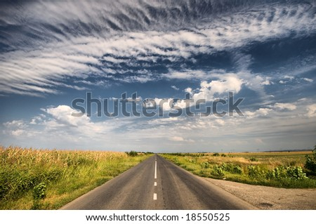 Empty country highway with summer cloudscape - stock photo