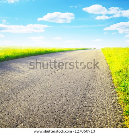 Empty country road on bright summer day. - stock photo