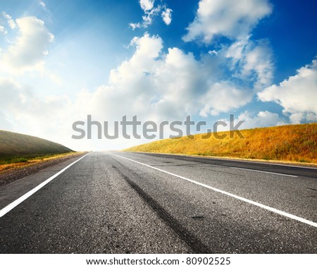 Empty countryside asphalt road and blue sky with clouds - stock photo