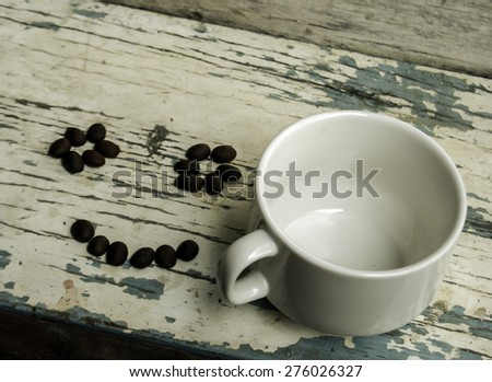 Empty cup of coffee with smiling coffee beans on the table - stock photo