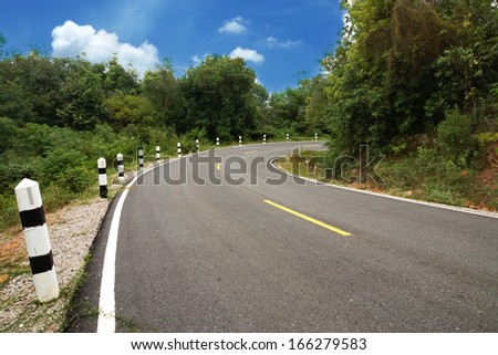 Empty curved road to the mountain. - stock photo