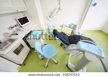 Empty dental clinic. Chair for patient, table with tools, computer and drill for dentist. - stock photo