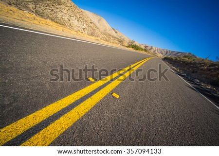 Empty desert highway leads into the mountains of the American southwest. - stock photo