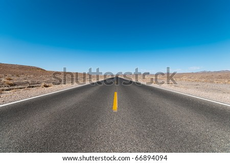 empty desert road in death valley with clear blue sky and copy space - stock photo