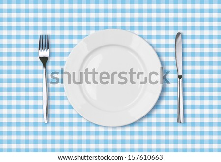empty dinner plate top view on blue picnic table cloth - stock photo