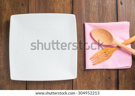empty dish, Wooden spoon and fork on a wooden table - stock photo