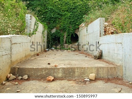 Empty dry drainage channel below town in hot summer period. Concrete bank covered by grass.  - stock photo