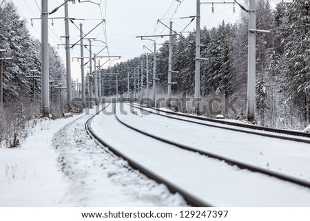 Empty electric railway line in winter forest - stock photo