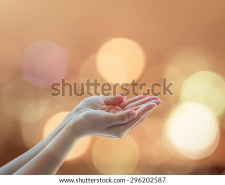 Empty female open human hands w/ palm up and golden candle light bokeh natural warm gold color tone: Pray for spirituality support helping meditation Night of power novel destiny: Prophet's birthday  - stock photo