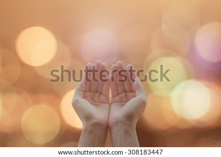 Empty female open human hands with palms up on blurred abstract background candle lights night bokeh natural warm gold color tone: Pray for peace concept: Humanitarian aid: World religion freedom day - stock photo