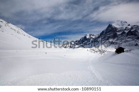 Empty field of snow with small hut - stock photo
