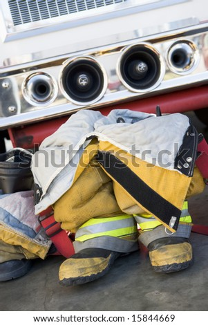 Empty firefighter's boots and uniform next to fire engine - stock photo