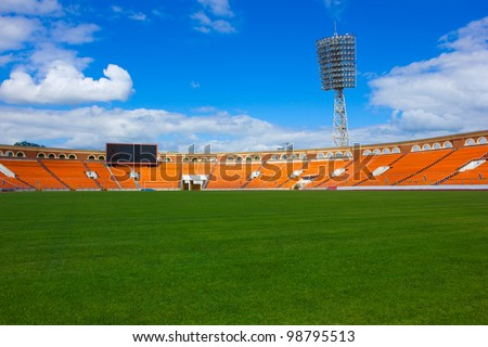 empty football field with score board and light stand - stock photo