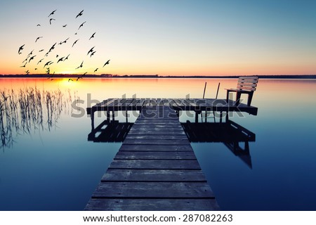 empty footbridge with a bench on a lake near Berlin at sunrise - stock photo