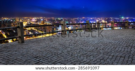 Empty footpath and panoramic modern skyline at night - stock photo