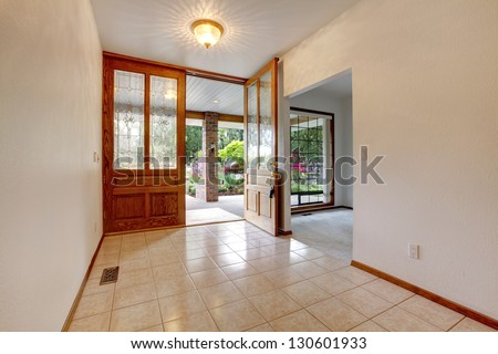 Empty front entrance with open door. Home interior with white walls. - stock photo