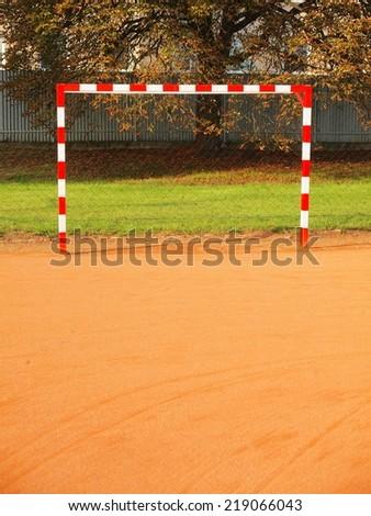 Empty gate. Outdoor football or handball playground, light red crushed bricks surface on ground - stock photo