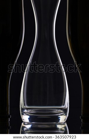 Empty glass and bottles on the black background - stock photo