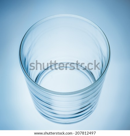 Empty glass, blue background, high angle view. - stock photo