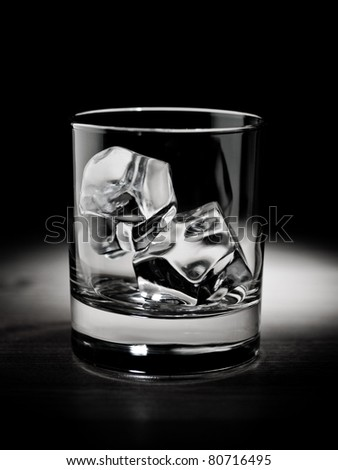 Empty glass filled with ice cubes; black and white - stock photo