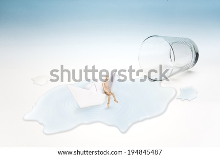 Empty glass of water with mannequins wait for help on paper boat (surreal concept) - stock photo
