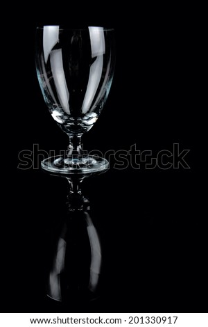 Empty glass with reflection on black background - stock photo