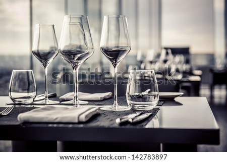 Empty glasses in restaurant, black and white photo  - stock photo