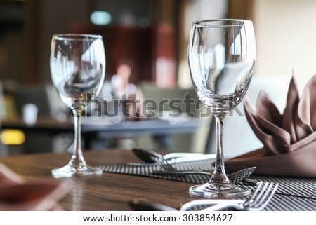 Empty glasses set in restaurant, Ambient lighting - stock photo