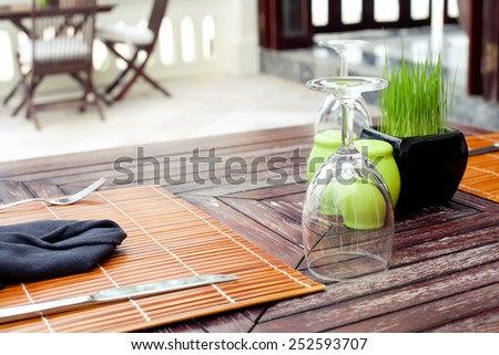 Empty glasses set in restaurant with a green grass - stock photo