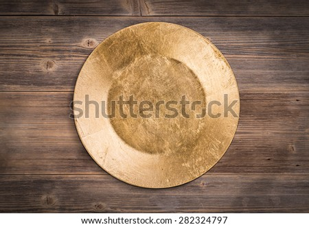Empty gold plate on wooden background - stock photo