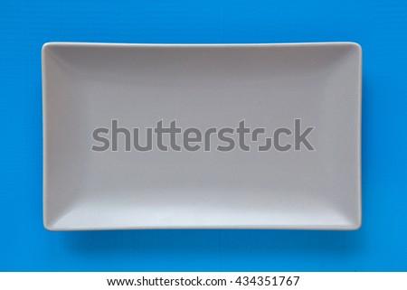 Empty gray ceramic dish on over blue background, rectangle dish - stock photo