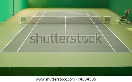 Empty green indoor tennis court - stock photo