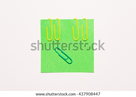 Empty green notepaper with yellow and green paper clip - stock photo