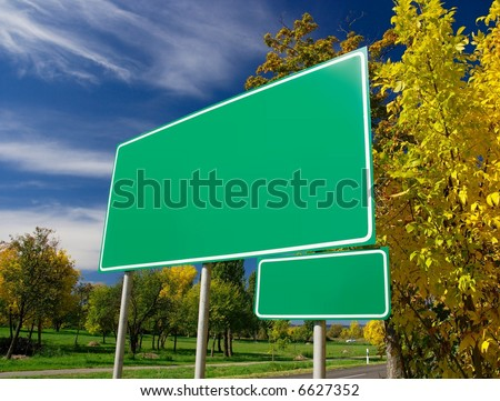 Empty green signboard at the roadside in an autumn landscape. Add your own text - stock photo