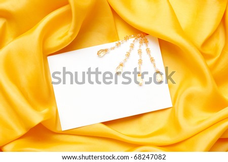 empty greeting card on yellow satin background - stock photo