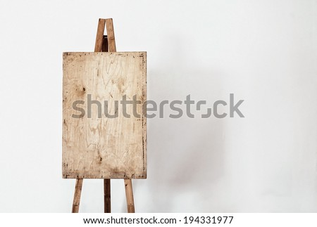 Empty grunge easel in a light room, art background - stock photo