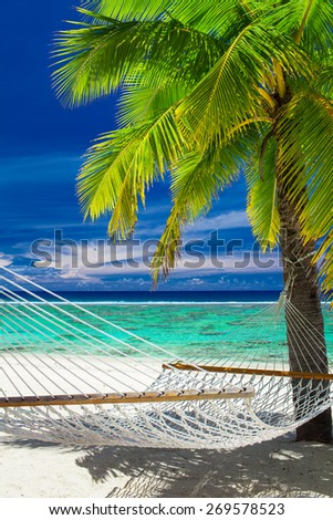 Empty hammock between palm trees on tropical beach of Rarotonga, Cook Islands - stock photo