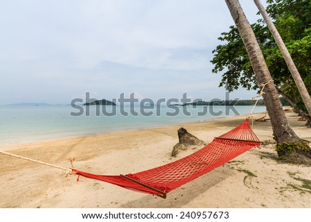 empty hammock hanging on coconut tree on the beach - stock photo