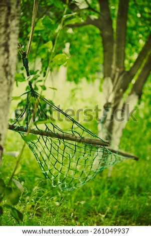 Empty hammock strung between two trees - stock photo