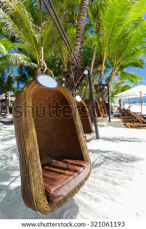 Empty hanging wicker chair on tropical beach, Philippines, Boracay  - stock photo
