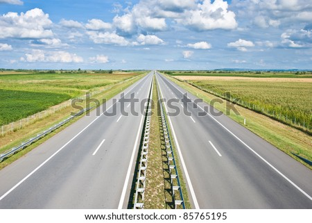 Empty highway and cloudy sky. - stock photo