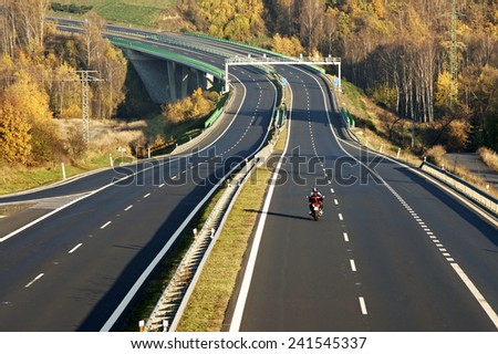 Empty highway leading across the bridge over the valley, in the foreground riding a motorcycle, electronic toll gates, deciduous forest in autumn colors, view from above - stock photo