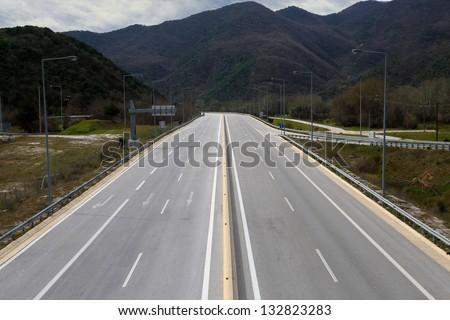 empty highway leading to a mountain range - stock photo